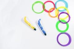 Zwei Stifte des Drucken 3d und bunte Fäden auf weißem Hintergrund Beschneidungspfad eingeschlossen Stockfoto