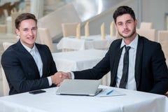 Zwei stilvoll und motivierte Geschäftsmänner rütteln Hände Lizenzfreie Stockfotografie