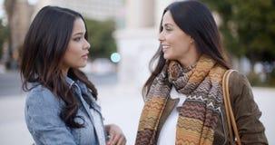 Zwei stilvolle Frauen, die draußen in einer Stadt plaudern Stockfotografie