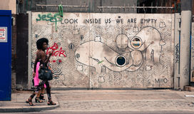 Zwei stilvolle Hippie-Mädchen, die vor einer Wand verziert mit Graffiti gehen Stockfotos