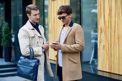 Zwei stilvolle Männer, die draußen plaudern lizenzfreies stockbild