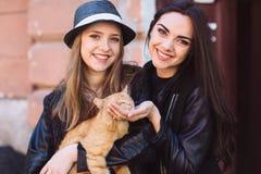 Zwei Straßenmädchen mit einer Katze Lizenzfreies Stockbild