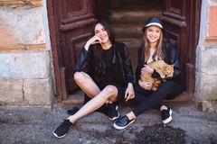 Zwei Straßenmädchen mit einer Katze Stockfotos