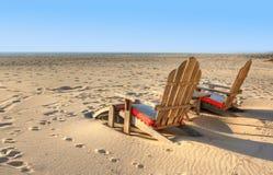 Zwei Strandstühle, die im Sand sitzen Stockbilder