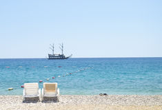 Zwei Strandstühle gegen blauen Himmel, azurblaues Wasser-, und altesseeschiff mit gelbem Sand auf einem Horizont Blauer Himmel un Lizenzfreies Stockfoto