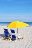 Zwei Strandstühle und -regenschirme auf dem Strand Lizenzfreie Stockbilder