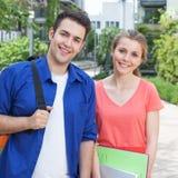 Zwei Studenten auf dem Campus, die über Kamera lachen Lizenzfreies Stockfoto