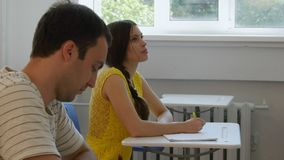 Zwei Studenten, die Anmerkungen in das Klassenzimmer schreiben Stockbild