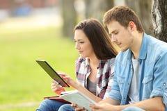 Zwei Studenten, die auf Linie studieren und Anmerkungen lesen Stockbild
