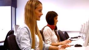 Zwei Studenten, die an Computern arbeiten stock footage