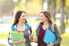 Zwei Studenten, die das Gehen in die Straße sprechen lizenzfreie stockbilder