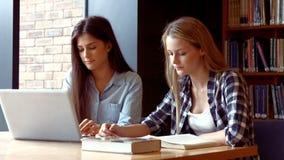 Zwei Studenten, die an einem Laptop arbeiten stock footage