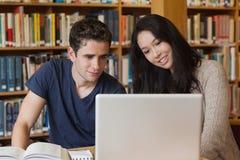 Zwei Studenten, die in einer Bibliothek mit einem Laptop lernen lizenzfreie stockfotos