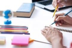 Zwei Studenten, die Hausarbeit tun und sitzend in einer Tabelle am Klassenzimmer sich helfen stockbild