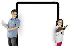 Zwei Studenten, die nahe einer leeren Anschlagtafel stehen Stockbilder