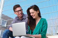 Zwei Studenten, die zusammen draußen an Laptop arbeiten Stockbild