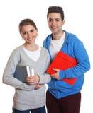 Zwei Studenten mit den Büchern und Schreibarbeit, die Kamera betrachten Stockfotografie