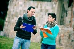 Zwei Studenten am Park mit Büchern auf Händen lizenzfreie stockbilder