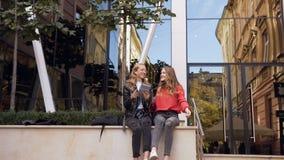 Zwei Studentenmädchen, die digitale Tablette am Freien verwenden Lächelnde Freundinnen, die über App auf Tablettengerät, Ausgabe  stock video footage