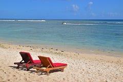 Zwei sundecks mit roten Kissen auf dem sandigen Strand, der sauberes Azurblaumeer mit Schnellboot im Hintergrund gegenüberstellt Stockbild