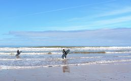Zwei Surfer, die ein Surfbrett auf dem Strand nahe Essaouira tragen stockbilder