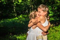 Zwei Töchter, die im Park umarmen lizenzfreie stockfotografie