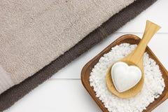 Zwei Tücher mit Schüssel füllten mit weißem Badesalze und hölzernem spoo stockbild