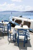Zwei Tabellen und Stühle in einem gemütlichen Restaurant auf dem Damm des alten Hafens in der griechischen Stadt von Fira Köstlic stockfotos