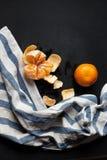 Zwei Tangerinen liegen auf der schwarzen Tabelle mit einem gestreiften Leinentuch Lizenzfreies Stockfoto