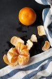 Zwei Tangerinen liegen auf der schwarzen Tabelle mit einem gestreiften Leinentuch Stockbild