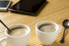 Zwei Tasse Kaffees auf dem Schreibtisch nahe bei dem Tablet-Computer und dem m Lizenzfreie Stockfotos