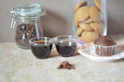 Zwei Tasse Kaffees auf dem Tisch Eine Tabelle mit Frühstücksplatte mit Muffin, auf einem Hintergrund eines Glases Kaffeebohnen Stockfotos