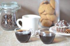 Zwei Tasse Kaffees auf dem Tisch Eine Tabelle mit Frühstücksplatte mit Muffin, auf einem Hintergrund eines Glases Kaffeebohnen Stockbilder