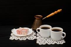 Zwei Tasse Kaffees auf den Spitzeservietten, den Töpfen und dem türkischen Nachtisch auf einem schwarzen Hintergrund Stockfotos