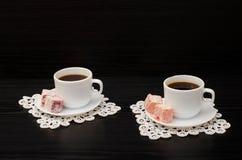 Zwei Tasse Kaffees auf den Spitzeservietten und türkischer Nachtisch auf einem schwarzen Hintergrund Lizenzfreie Stockfotos