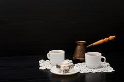Zwei Tasse Kaffees auf weißen Servietten, Töpfen und türkischen Bonbons auf einem schwarzen Hintergrund lizenzfreies stockbild