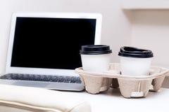 Zwei Tasse Kaffees, die auf einer weißen Tabelle und einem Notizbuch stehen Lizenzfreie Stockbilder