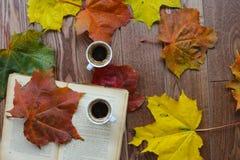 Zwei Tasse Kaffees, ein Buch und Herbstlaub auf einem braunen Holztisch Lizenzfreies Stockfoto