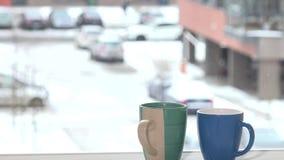 Zwei Tasse Kaffees heiße Getränk-Stand des Tees auf Fensterbrett- und Schneeflockenschneefall stock video