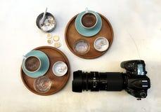 Zwei Tasse Kaffees, Kamera und Aschenbecher mit einer Zigarette sind auf dem Tisch lizenzfreies stockfoto