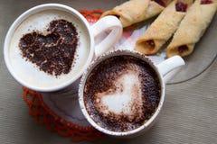Zwei Tasse Kaffees mit einem Herzen gemalt auf der Oberfläche und den Plätzchen Lizenzfreie Stockfotos