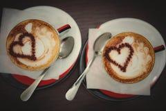 Zwei Tasse Kaffees mit Herzmuster Stockbilder