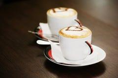 Zwei Tasse Kaffees mit Herzmuster Stockfotografie