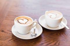 Zwei Tasse Kaffees mit Herzmuster Stockbild