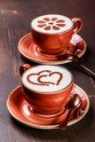 Zwei Tasse Kaffees mit Muster auf hölzernem Hintergrund Lizenzfreie Stockfotografie