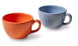 Zwei Tasse Kaffees, Orange und Blau auf einem weißen Hintergrund Lizenzfreies Stockbild