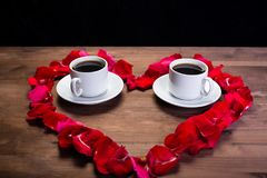 Zwei Tasse Kaffees sind auf dem Tisch innerhalb des Herzens der Rose Stockbilder