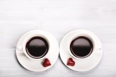 Zwei Tasse Kaffees und geformte Bonbons des Herzens Stockfotos