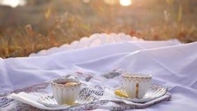 Zwei Tassen Tee mit Zitrone bei Sonnenuntergang stock footage