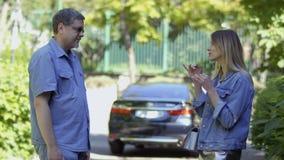 Zwei taub-stumme Leute, die an unscharfem Autohintergrund im Park sprechen stock video
